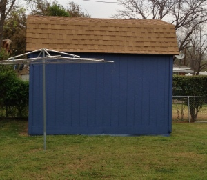 A 'cloud blue' storage shed with brown shingled roof. A rotary clothesline is in front and to the left of the shed.