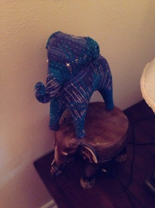 Stuffed fabric elephant statue with cross hatched blue, black, and grey stripes. Elephant is standing on a carved wood elephant plant stand.