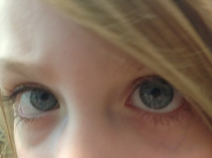 Close up photo showing only the bright blue eyes eyes of young child. Blonde hair falls over part of the left eye.