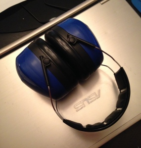 Blue noise canceling ear muffs on top of a closed laptop.