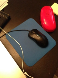 Blue mousepad on a black table. A black mouse sits atop the mousepad, and a red glasses case sits to the right.