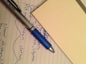 Sideways notebook with a list of Activities for Daily Living. Those notes are partially covered by a blue pen and an upside down checkbook.