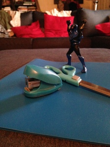 Blue folder underneath a blue mini stapler, blue handled scissors, and a blue and black Venom action figure.